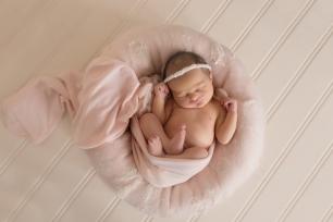 baby girl smirk in pink nest