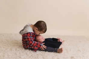 big brother kissing new baby