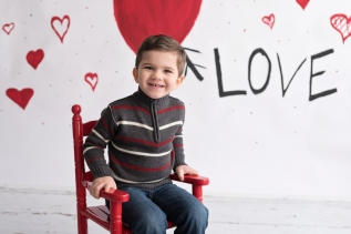 valentines day mini boy in red rocking chair