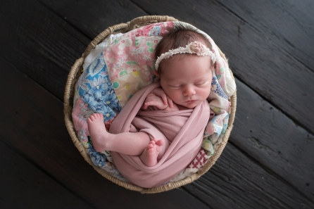 baby in basket with a quilt
