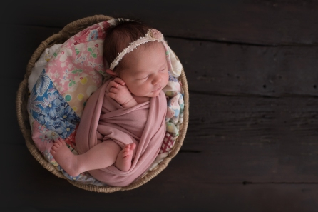 baby in basket with quilt side light