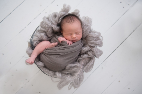 baby in basket in gray