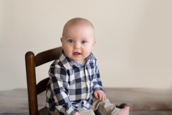happy boy sitting in wooden chair