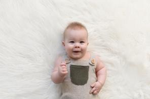 baby boy smiling on white blanket
