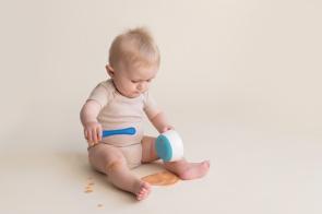 boy feeding himself baby food