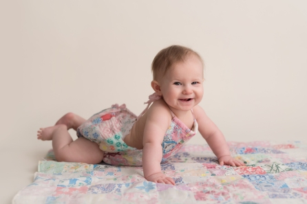 baby in quilt romper pushing up
