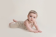 serious baby girl on belly in romper